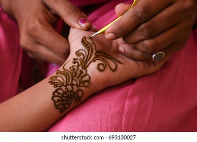 Artist applying beautiful henna tattoo Arabic design to a Woman's or Indian bride's hands at City Palace on wedding in Rajasthan. Mehndi is a popular body art among women of India, Pakistan, Africa.