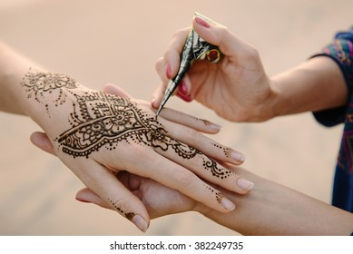 Artist applying henna tattoo on women hands. Mehndi is traditional Indian decorative art. Close-up