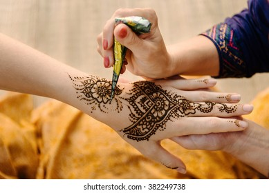 Artist applying henna tattoo on women hands. Mehndi is traditional Indian decorative art. Close-up, overhead view