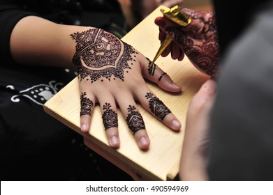 Artist applying henna tattoo on women hands.