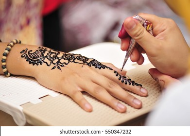 Artist applying henna tattoo on bride hands. Mehndi is traditional Indian decorative art. Close-up