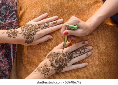 Artist applying henna tattoo on women hands. Mehndi is traditional Indian decorative art. Close-up, top view