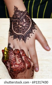 Artist applying henna tattoo on bride hands. Mehndi is traditional Indian decorative art. Close-up - shallow depth of field