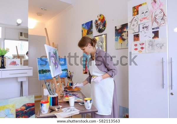 Artist attractive woman of European appearance writes oil painting, enjoying things what love , paint picture for sales and order, listening to music on headphones through phone, stands and works in