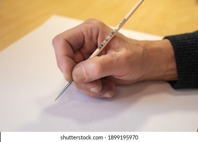 The artist begins to paint a picture. Artist's hand with a paintbrush on a white sheet background. The hand of the old master.