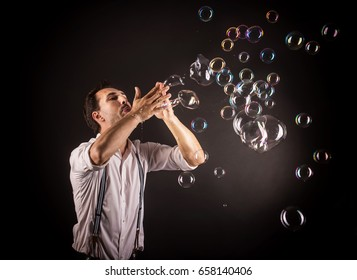 Artist blowing many soap bubble from his hands. Bubble show studio concept.