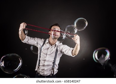 Artist blowing many soap bubbles from his hands. Bubble show studio concept.
