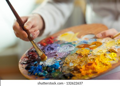 artist brush mix color oil painting on palette is holding in his hand closeup