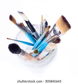 Artist brushes in a glass jar - view from the top. Isolated over white background.