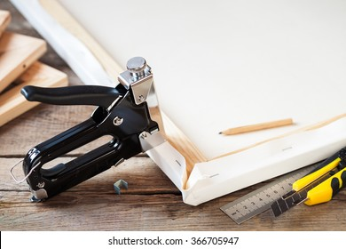Artist canvas, canvas stretcher and staple gun on table