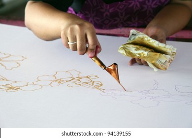 An artist carefully trace the floral motif on a traditional batik fabric using melted wax