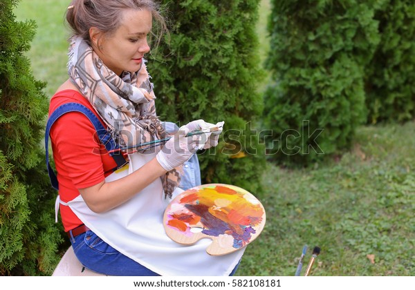 Artist cleans workplace, evaluate work that stands on easel, smiling, posing and looking in camera, sits on chair in park outdoors on background of coniferous plants in afternoon. Girl dressed in red