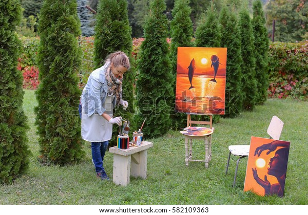 Artist cleans workplace, evaluate work that stands on easel, smiling, posing and looking in camera, standing in full length near paintings in park outdoors on background of coniferous plants in