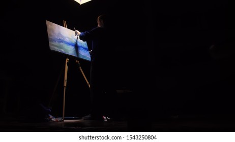 Artist copyist paint seascape with ship in ocean. Craftsman decorator draw as boat sail on blue sea with acrylic oil color. Black background. Indoor. Wide angle shot cinematic look.