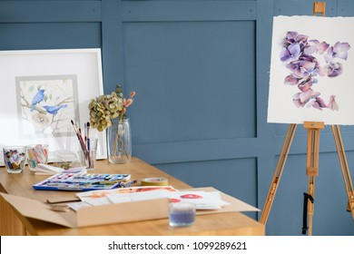 artist creative workspace. inks papers and tools on the table. watercolor floral painting on an easel and finished framed drawing of birds.