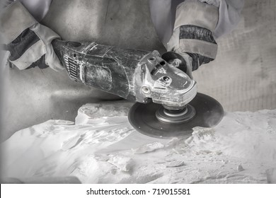 Artist cutting marble stone with angle sander and diamond disc