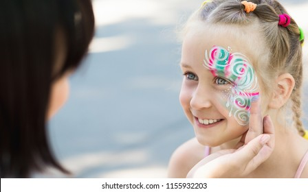 Artist decorating little girl face painting with glitter, happy outdoor walk, copy space