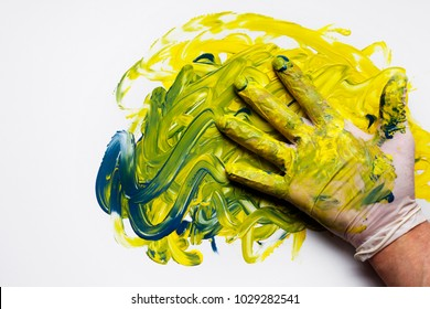 Artist dips gloved hand into several paint pots and creates his own canvas art