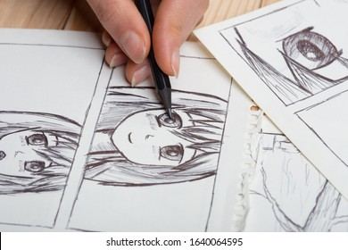 Artist drawing an anime comic book in a studio.