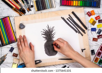 Artist is drawing charcoal pineapple sketch. Workplace of artist background. Top view of painter tools - pencils, brushes, palette and watercolor paint collection