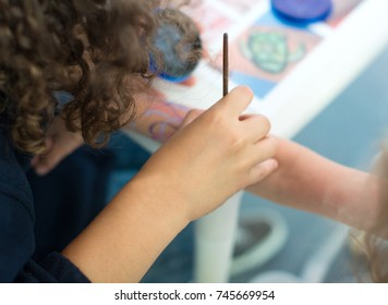 Artist drawing octopus on the child's hand.