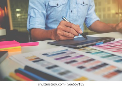 Artist drawing on graphic tablet with color swatches in office. Architectural drawing with work tools and accessories.