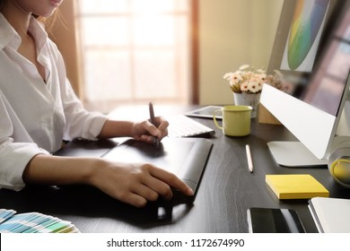 Artist drawing something on graphic tablet with creative desk at the office.