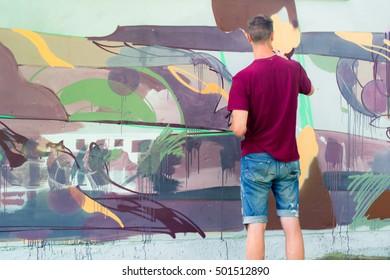 The artist draws graffiti on a fence.