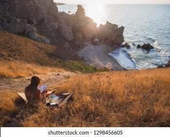 The artist draws the sea, Rus sea bay. Downstairs is her tent. She lives in a tent by the sea in a shell bay. Wakes up in the morning and sees the sea. Here you can sometimes see dolphins.