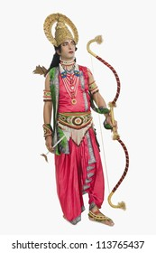 Artist dressed-up as Rama and holding a bow and arrow