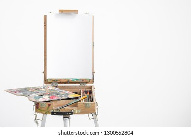 Artist easel with blank canvas on a white background. Place for text.