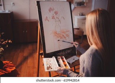 Artist, a European girl, paints painting on canvas with watercolor in her workshop and art school.