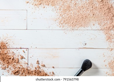 Artist face brush for natural beauty and cosmetics background with still life of smashed makeup powder on white wooden background, copy space for text, above view