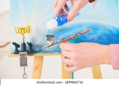 Artist fills the airbrush canister with blue paint. An easel with a painting is visible in the background