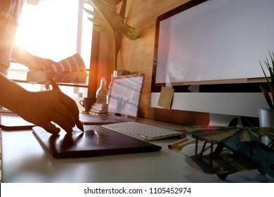 Artist graphic designer working on digital tablet in studio office.