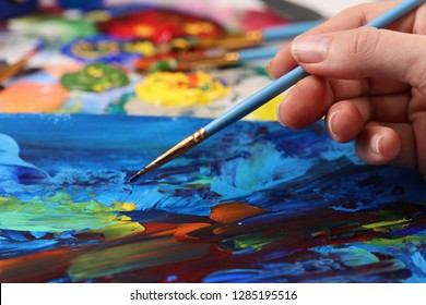 Artist hand with brush painting picture close up. Art, creativity, hobby concept, Anti stress art therapy .