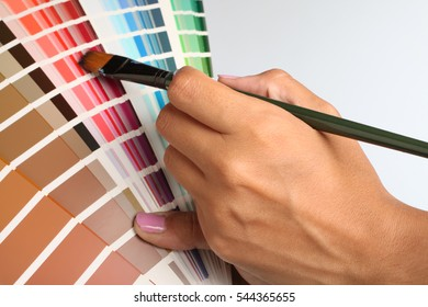 Artist hand with paintbrush pointing to color samples in palette on white background