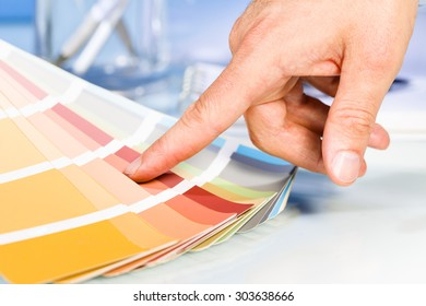 Artist hand pointing with finger to color samples in palette in studio background