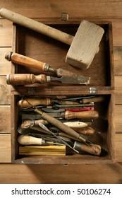 artist hand tools for handcraft works on golden wood background