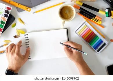 Artist hands sketching on blank notebook on creative workspace.
