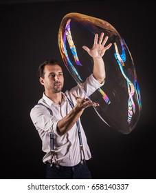 Artist hold big soap bubble in his hands. Bubble show studio concept.