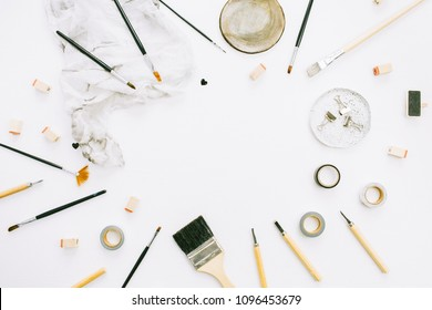 Artist home office desk workspace frame paint brushes and tools on white background. Flat lay, top view creative minimal mock up template.
