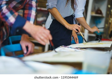 Artist makes the brush strokes on a canvas while painting a watercolor. Pupils in art school paint on canvas with watercolors. Artists hands with a brush over the canvas. Concept school of painting.