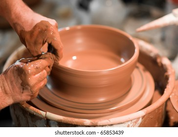 An artist makes clay pottery on a spin wheel.