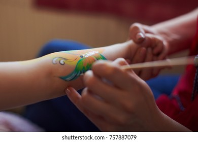 Artist is making butterfly picture on kids birhtday