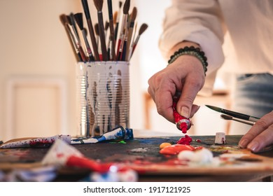 Artist mixing acrylic colors on palette for painting. Woman working in her art studio