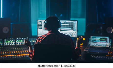 Artist, Musician, Audio Engineer, Producer in Music Record Studio, Uses Control Desk with Computer Screen showing Software UI with Song Playing. Success with Raised Hands, Dances. Back View.