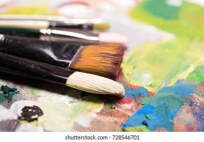Artist paint brushes and oil paint  on wooden artistic palette background. Brush paint artistic. Tools for creative work. Back to school. Paintings Art Concept. Selective focus. Copy space.