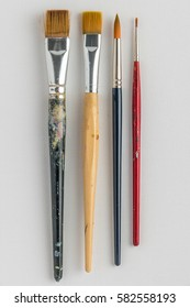 Artist paint brushes on canvas background. Top view with copy space.