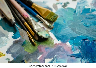 Artist paint brushes on wooden palette. Texture mixed oil paints in different colors. Instruments tools for creative leisure. Painting hobby background. Paintings art concept. Copy space.